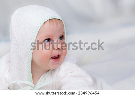 Smiling boy in white bathrobe lying on sofa, close up - stock photo