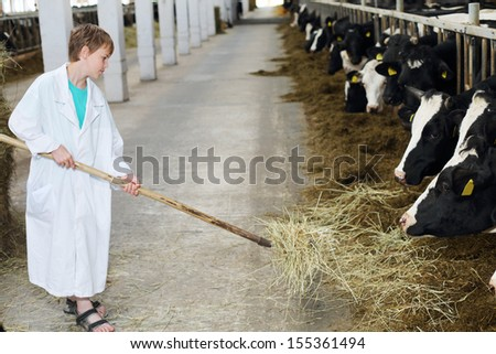 Smiling boy in white coat loads hay by big pitchfork for cows at large farm.  - stock photo