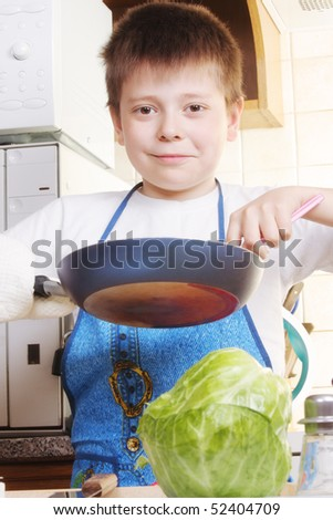 Smiling boy in white shirt standing in kitchen with frying-pan