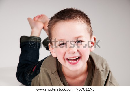 smiling boy laying down bare foot - stock photo