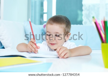 Smiling boy looking at his drawing while sitting by table - stock photo