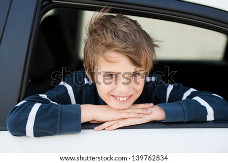 Smiling boy looking out the car in a close up image - stock photo