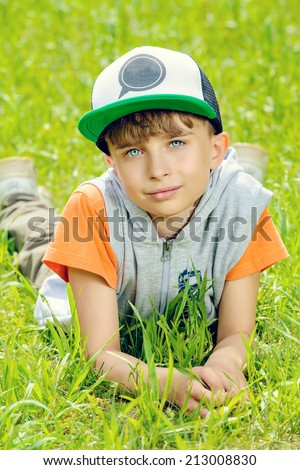 Smiling boy lying on a grass at a park. Summer day.  - stock photo
