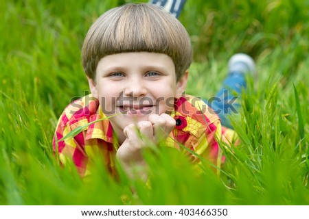 Smiling boy lying on the grass in the park, springtime