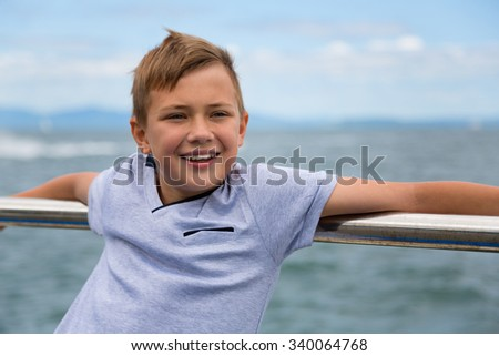 Smiling boy on the background of the sea - stock photo
