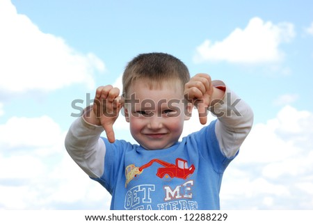 Smiling boy over cloudy blue sky showing some gesture - stock photo
