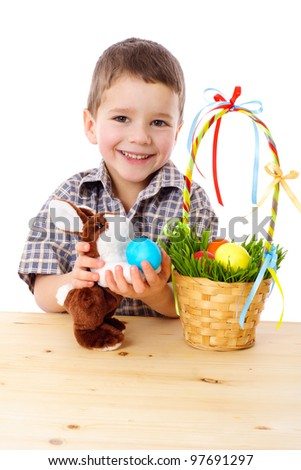 Smiling boy playing with easter eggs and bunny, isolated on white