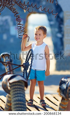 smiling boy pretending a driver of imaginary vehicle - stock photo