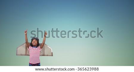 Smiling boy pretending to be pilot against dark blue green background - stock photo