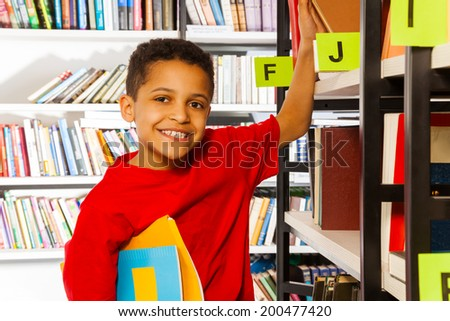 Smiling boy puts hand on bookshelf and holds book - stock photo