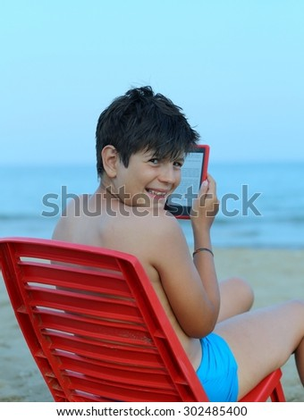 smiling boy reads the ebook on the seashore in summer - stock photo