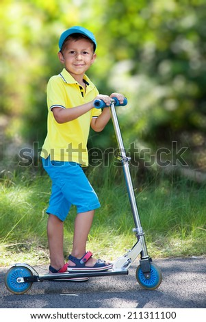 Smiling boy riding a scooter in the park. - stock photo