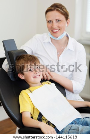 Smiling boy sitting in a dentist's chair and smiling dentist - stock photo