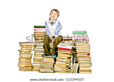 Smiling boy sitting on a pile of books. Education. Isolated over white.