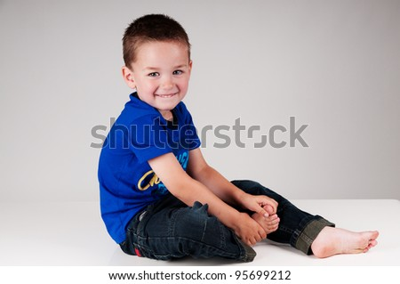 smiling boy sitting on a table - stock photo