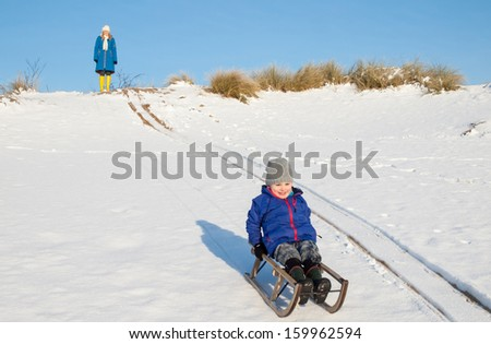Smiling boy sledging down a snow covered dune with woman watching in the background