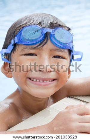 smiling boy soaking in the pool