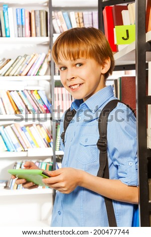 Smiling boy stands and holds books in library - stock photo