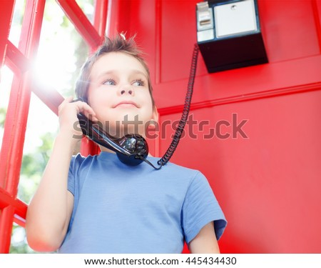 smiling boy stands in a red telephone box. concept of sharing emotions, impressions and feelings. happy child holding a telephone handset and wait for a phone call in a red telephone booth. old school - stock photo