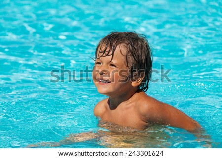 Smiling boy swimming in pool and looking to the right - stock photo