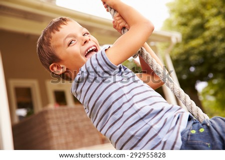 Smiling boy swinging on a rope at a playground - stock photo