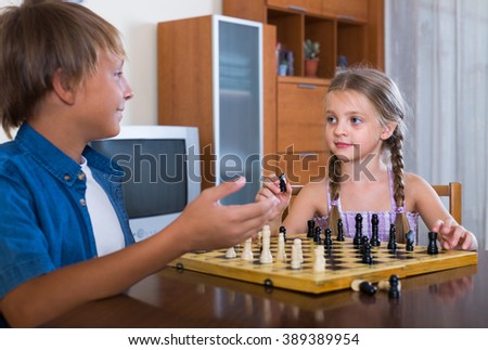 Smiling boy teaching cute little sister chess game at home - stock photo