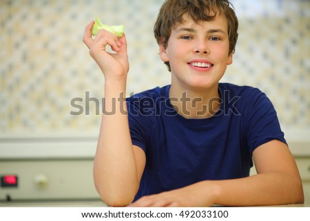 Smiling boy teenager in dark blue shirt holds stub of green apple, close up view