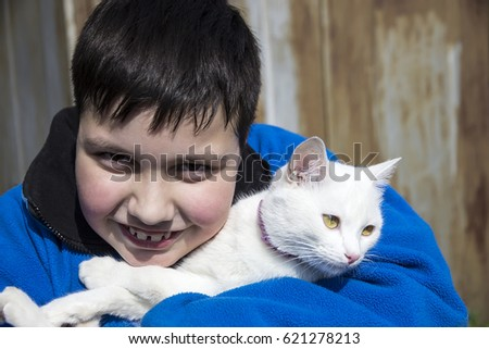 Smiling Boy teenager Plump build In a blue sweater holds a white cat in his arms.