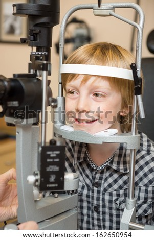 Smiling boy undergoing eye examination test with slit lamp in store - stock photo