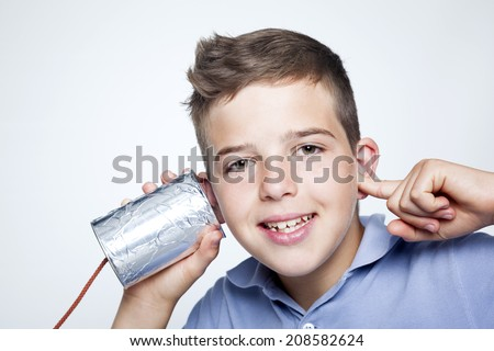 Smiling boy using a can as telephone against gray background - stock photo
