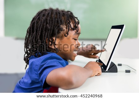 Smiling boy using digital tablet in classroom - stock photo