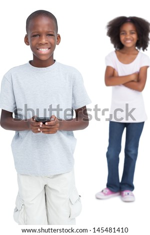 Smiling boy using mobile phone with his sister behind him