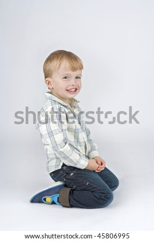 Smiling boy which kneels,on white background.