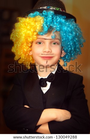Smiling boy with a funny wig in a suit - stock photo