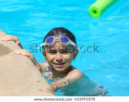 Smiling boy with a mask for snorkeling in the pool