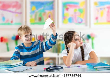 Smiling boy with a paper plane and bored girl sitting by the table  - stock photo