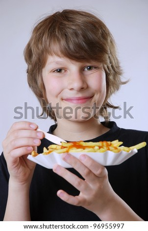 smiling boy with a paper plate of french fries