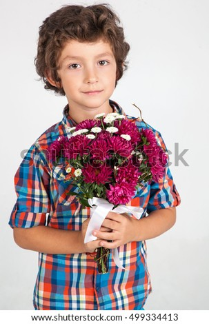 Smiling boy with bouquet of flowers on white background.