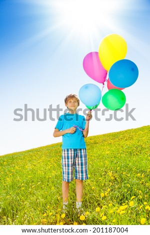 Smiling boy with colorful balloons stand in field