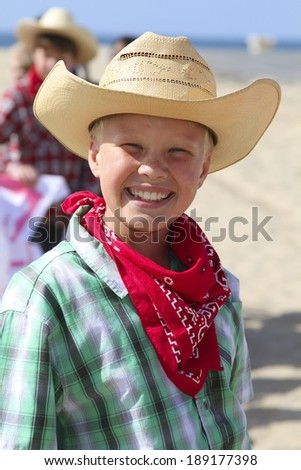 Smiling Boy with Cowboy Hat, Bandana and Plaid Shirt Ready for a Hoedown - stock photo