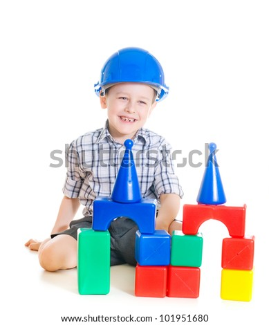 smiling boy with hard hat playing with building blocks - stock photo