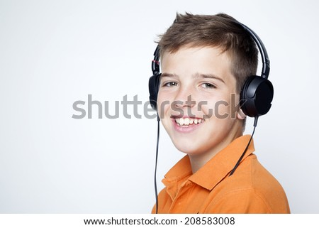 Smiling boy with headphones listening music against grey background