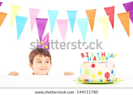 Smiling boy with party hat looking at a birthday cake isolated on white background - stock photo