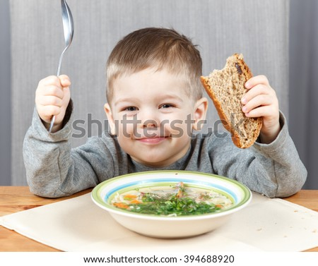 Smiling boy with plate of soup for dinner
