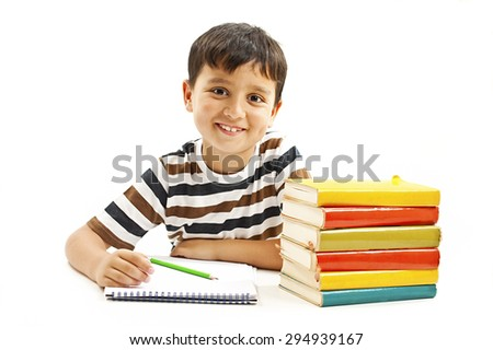 Smiling boy with school books on the table.  Isolated on a white background