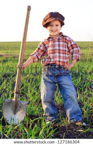 Smiling boy with shovel in field - stock photo