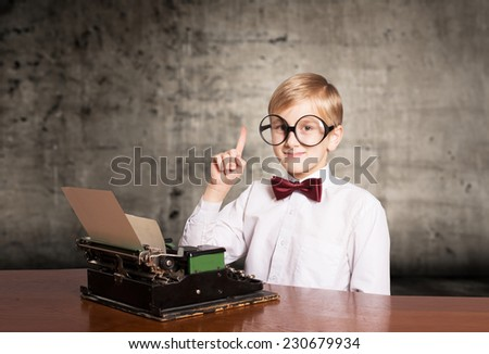 Smiling boy with the old typewriter raising the index finger up. Retro style portrait - stock photo
