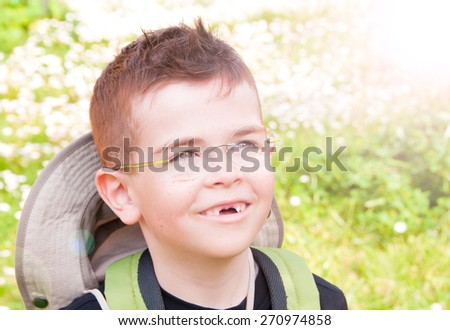 Smiling boy without front teeth looking at the sun