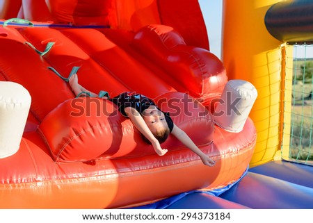 Smiling boy (7-9 years) wearing black t-shirt lies upside down on slide of red bouncy castle - stock photo
