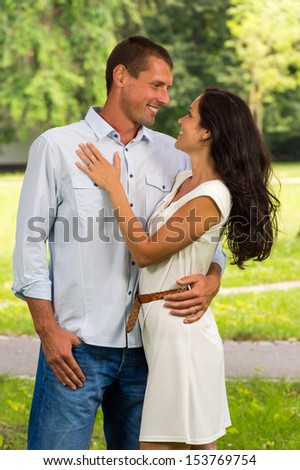 Smiling boyfriend and girlfriend embracing outdoors - stock photo